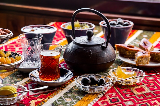 Вид сбоку чугунный чайник с вареньем и чашкой чая