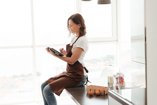 Side view of casual woman in apron sitting on table and using tablet computer