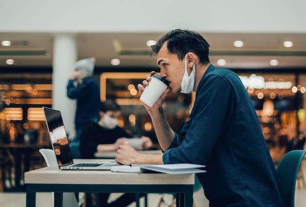 側面図。カフェのテーブルに座ってコーヒーテイクアウトとカジュアルな若い男