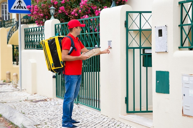 Side view of caucasian courier ringing in doorbell. pensive postman wearing red uniform, carrying yellow thermal bag, holding package and standing outdoors. delivery service and post concept