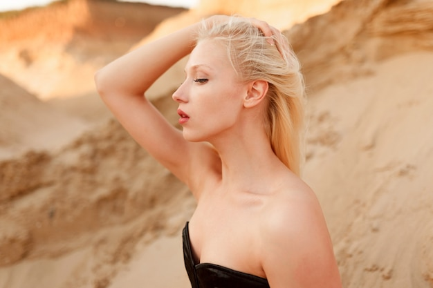 Side view of a caucasian female model with blond hair and makeup, in black sexy bodysuit, touching her hair, seated on the sand in desert.
