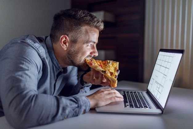 Side view of caucasian hardworking architect eating pizza and using laptop while sitting in office late at night.