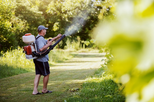 Side view of caucasian mature peasant in working clothes, hat and with modern pesticide spray machine on backs spraying bugs in vineyard.