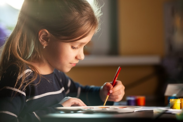 Side view of charming little caucasian smiling schoolgirl writes while sitting at table. little cute girl draws picture.