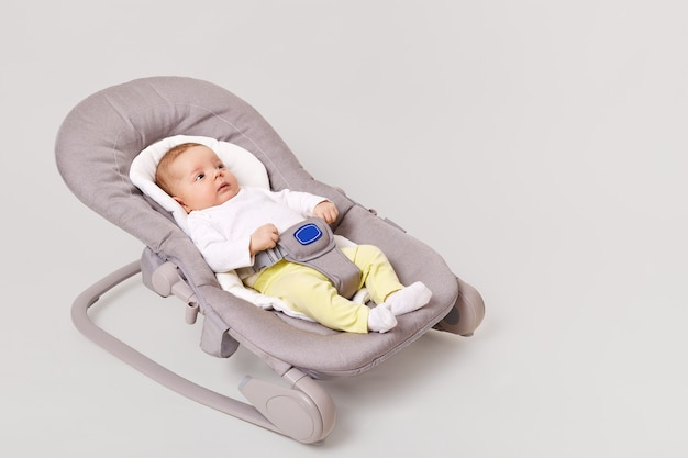 Vista laterale dell'affascinante ragazza appena nata che si trova nella sedia del buttafuori di rimbalzo