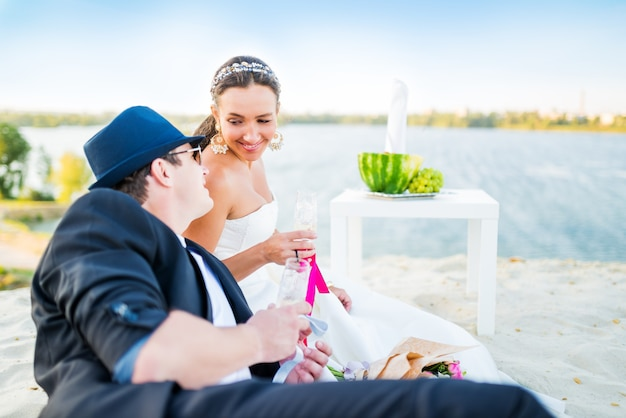 Side view of charming young couple bride and groom clink glasses of champagne while sitting at table with fruits and bouquet of flowers