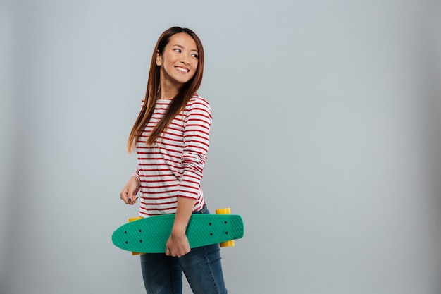 Side view of cheerful asian woman in sweater holding skateboard