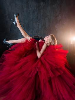 La vista laterale della bionda allegra in un vestito rosso lussureggiante si siede su una sedia e alza le gambe