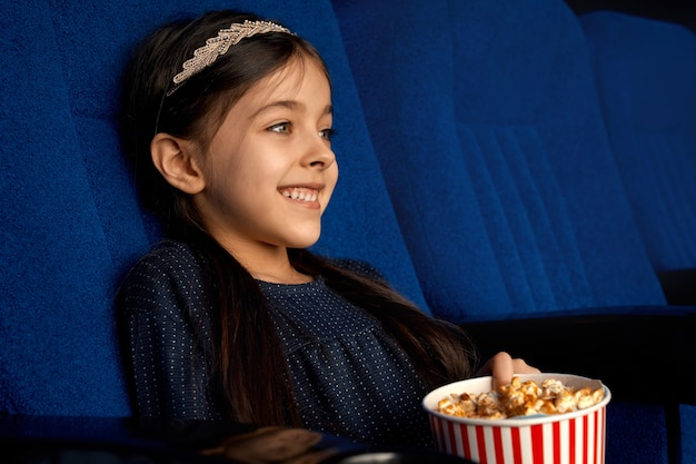 Side view of cheerful brunette girl with ponnytail laughing at funny comedy in cinema. happy female child eating popcorn and relaxing on weekend