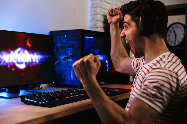 Side view of cheerful gamer playing video games on computer