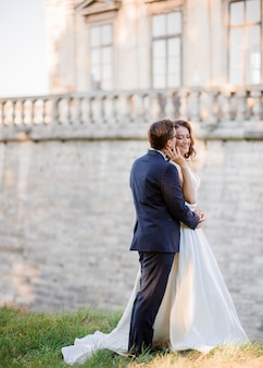 Side view of cheerful groom and bride, standing near ancient architecture build, holding by hands and enjoying their happy romantic moments
