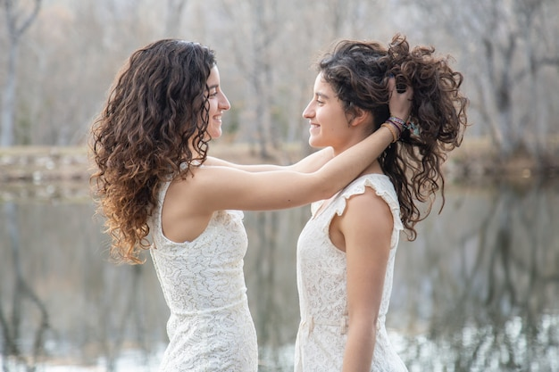 Side view of cheerful twin sisters smiling and combing hair to each other