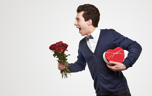Side view of cheerful young romantic guy in elegant outfit carrying bouquet of red roses and heart shaped gift box, while rushing to date