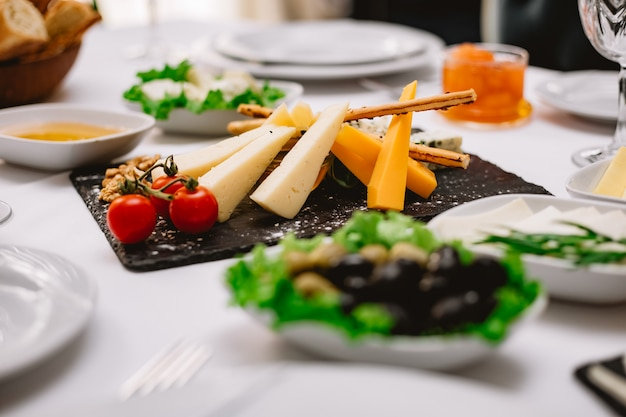 Side view cheese plate with tomatoes and nuts