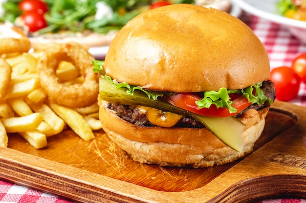 サイドビューチーズバーガーグリルビーフパティピクルスキュウリフレッシュトマトレタスチーズのハンバーガーパンフライドポテトとオニオンリングテーブルの上