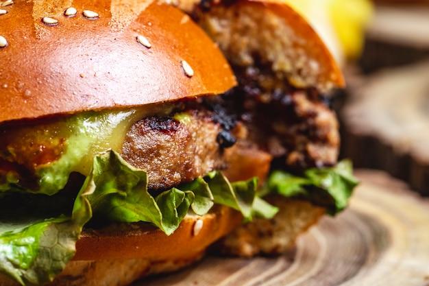 Вид сбоку чизбургер на гриле, котлета из говядины с сыром и листьями салата между булочками с бургером