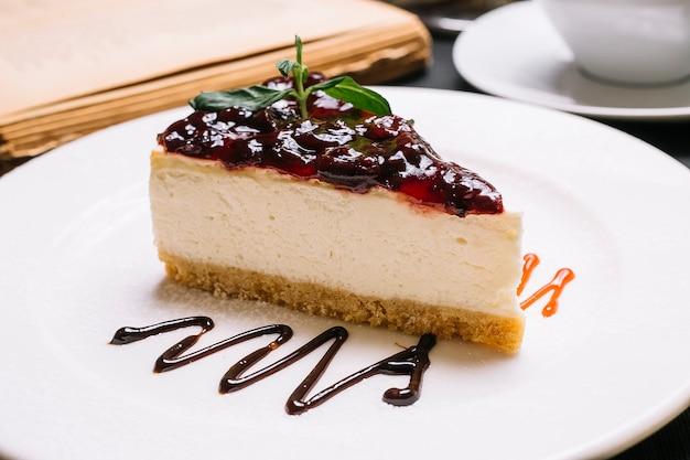 Vista laterale della cheesecake con gelatina di ciliegie sulla parte superiore su un piatto bianco