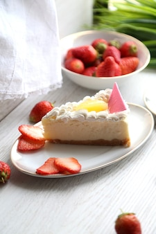 Side view cheesecake with cream and strawberries