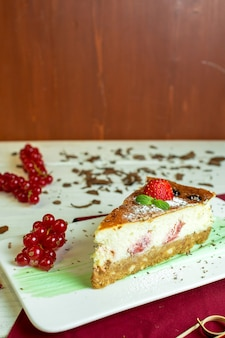 Cheesecake vista laterale con ribes rosso