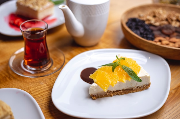 Side view cheesecake with slices of orange and a glass of tea
