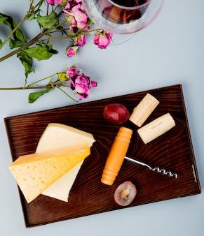 Vista laterale di formaggi come cheddar e parmigiano con tappi d'uva e cavatappi sul tagliere e fiori su bianco 1