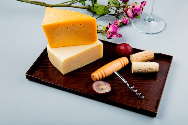 Side view of cheeses as cheddar and parmesan with grape corks and corkscrew on cutting board and flowers on white