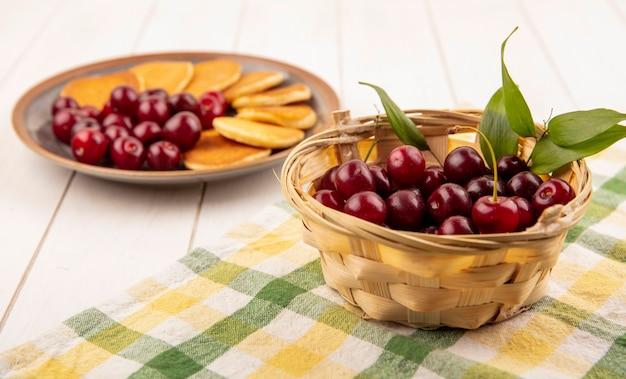 Vista laterale della merce nel cestino delle ciliegie su un panno plaid e piatto di frittelle e ciliegie su fondo di legno