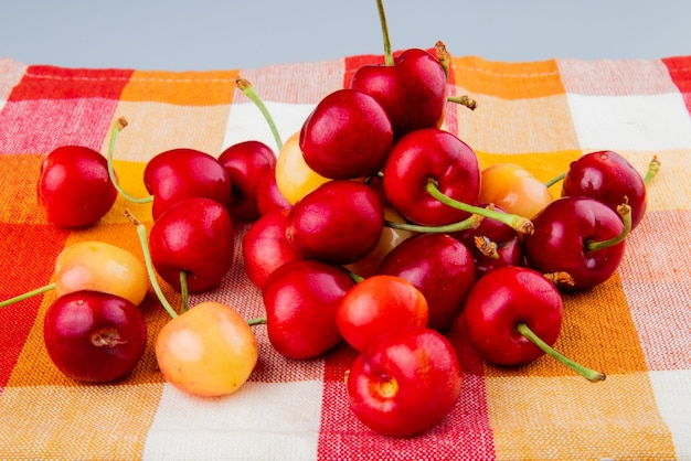 Side view of cherries on plaid cloth and white table