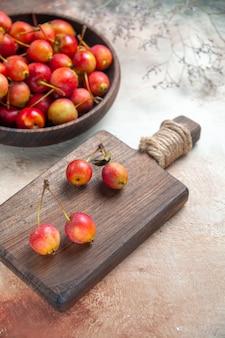 Вид сбоку вишни на разделочной доске с ягодами чаша из веток вишни
