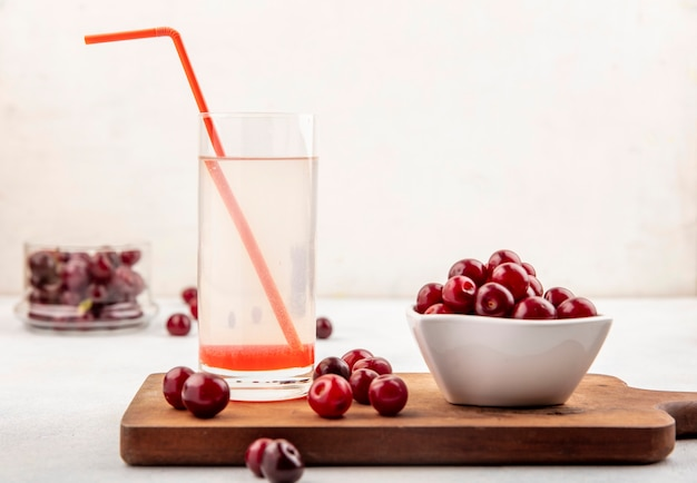 Side view of cherry juice with drinking tube in glass and cherries in bowl and on cutting board and on white background