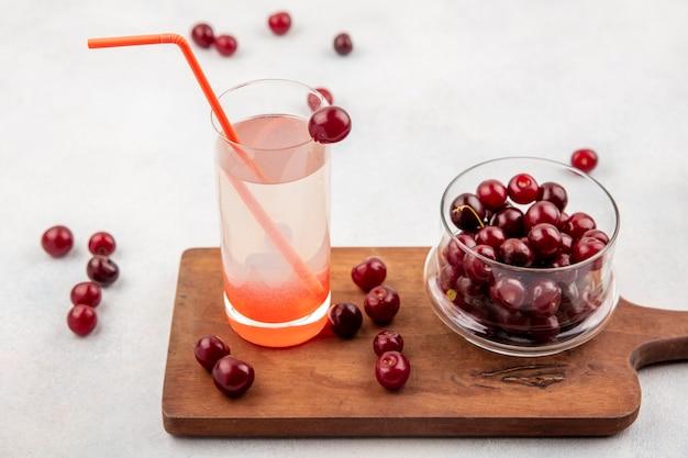 Vista laterale del succo di ciliegia con tubo per bere in vetro e ciliegie in vaso e sul tagliere e su sfondo bianco