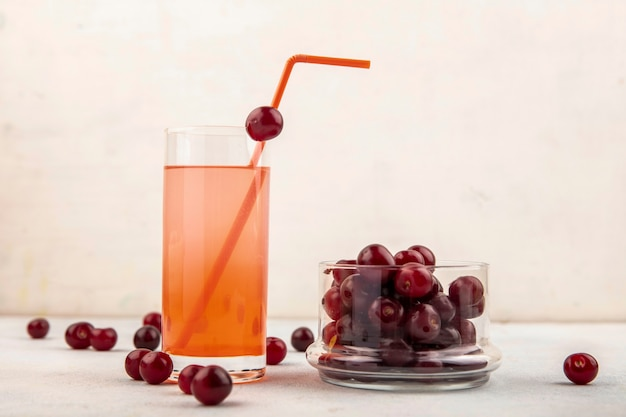 Side view of cherry juice with drinking tube in glass and cherries in jar and on white background