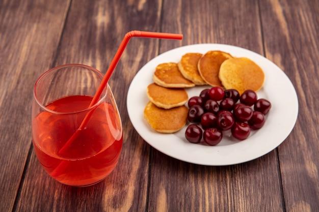 Vista laterale del succo di ciliegia con tubo per bere in vetro e piatto di frittelle e ciliegie su fondo di legno