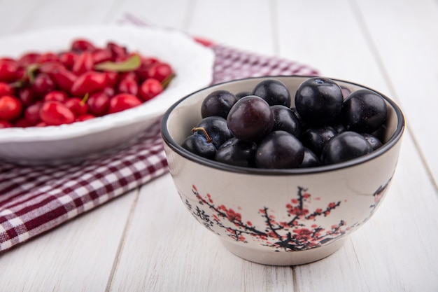Side view cherry plum in a bowl with dogwood on a plate