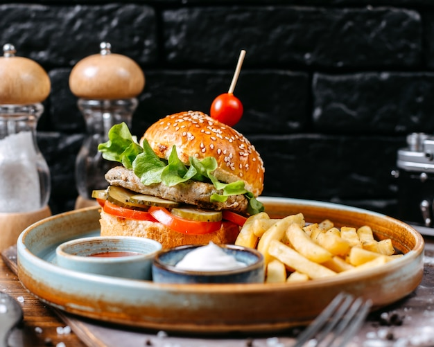 Side view of chicken burger with pickles and tomatoes served with french fries and sauces on dark