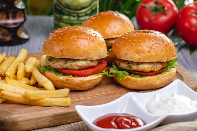 Side view chicken burgers with french fries ketchup and mayonnaise on the board