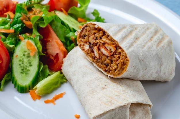 Вид сбоку куриное буррито на гриле куриное филе с рисом, завернутым в тортилью, свежие огурцы, помидор, морковь и салат на тарелке