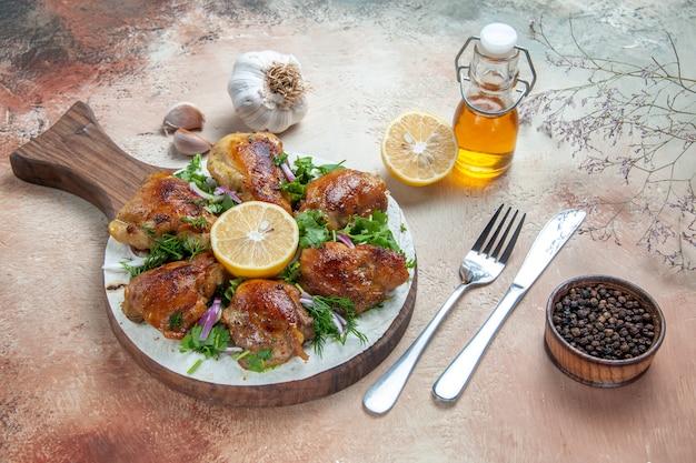 Vista laterale pollo pollo con erbe aromatiche cipolla limone sulla tavola coltello forchetta olio aglio pepe nero