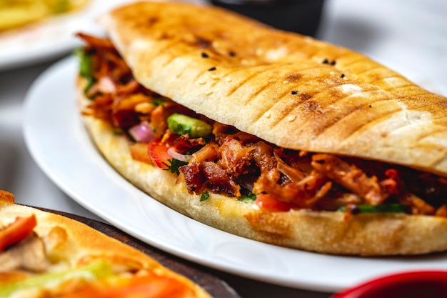 Side view chicken doner grilled chicken with cucumber tomato greens red onion and sauce in a bread