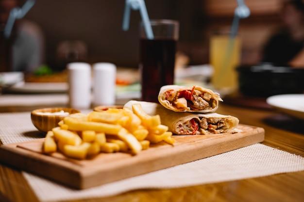 Вид сбоку куриный донер в лаваше с картофелем фри с кетчупом и майонезом на доске