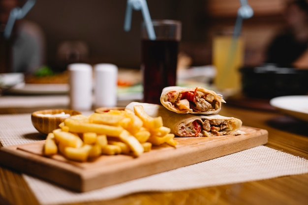 Side view chicken doner in pita bread with french fries with ketchup and mayonnaise on the board