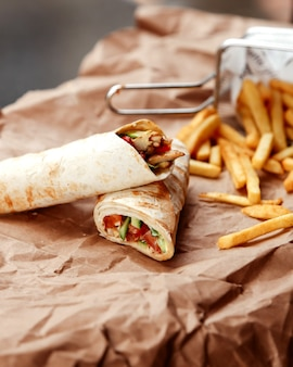 Side view chicken doner in pita bread with french fries