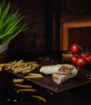 Side view of chicken doner wrapped in lavash and french fries on a wooden cutting board