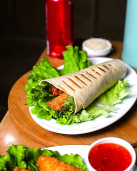 Side view of chicken doner wrapped in lavash on lettuce on wooden table