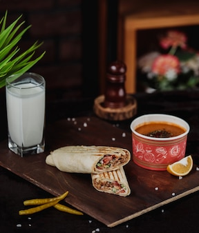 Side view of chicken doner wrapped in lavash served with lentil merci soup and ayran drink on a wooden board