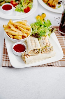 Side view of chicken doner wrapped in lavash with french fries