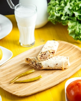 Side view of chicken doner wrapped in lavash with pickled green pepper on wooden platter