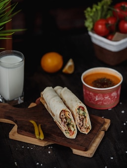 Side view of chicken doner wrapped in lavash on a wooden board served with lintel soup and ayran drink on the table