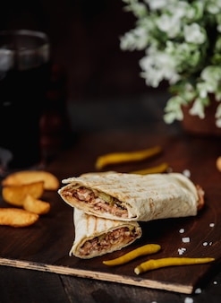 Side view of chicken doner wrapped in lavash on a wooden cutting board