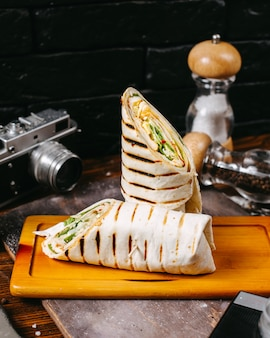 Side view of chicken doner wrapped in lavash on wooden table